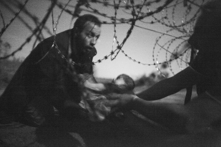 A man passes a baby through the fence at the Hungarian-Serbian border in Röszke, Hungary, 28 August 2015. © Warren Richardson, Australia (source: worldpressphoto.org)