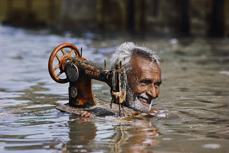 """Tailor in Monsoon, Porbandar, India, 1983 National Geographic. December 1984. MAX PRINT SIZE: 40x60 Tailor carries his sewing machine through monsoon floodwaters. -India Book (pg. 139) Tailor carrying his sewing machine, Porbandar, India, 1983 -Untold (pg. 66 - 67) Monsoons: Life Breath of Half the World, Vol. 166, No. 6""""McCurry has the artistry to free photography from its anchor in the particular event, in the often mundane facts of occurrence at such and such a precise time and place. There is no question that the photograph has a distinct power in proving its pint, in revealing precise detail. It usually has a more difficult tie creating principles, moving from the discreet instance to the more general application. McCurry makes photographs that make this leap. This picture depicts more than the surrealism of a man up to his neck in water carrying a sewing machine. It is also a picture about the grace in a time of trouble, about acceptance, and about endurance. This is likely to be neither the first monsoon the smiling man has experienced, nor the last."""" - Phaidon 55 final print_milan, iconic photographs Whether it is children using a war-ravaged landscape as a playground or merchants continuing their trade in bomb-damaged buildings, McCurry has documented how individuals can adapt to the most extraordinary of circumstances. Such is the case in this image of a cheerful tailor carrying his rusted sewing machine through the deep monsoon waters. Monsoon_BookSteve Mccurry_Book Iconic_Book Untold_book final print_MACRO final print_Sao Paulo final print_Birmingham final print_HERMITAGE final print_Zurich final print_Ankara India_Book final print_Rubin retouched_Sonny Fabbri 6/2015 Fine Art Print MAX PRINT SIZE: 40X60"""
