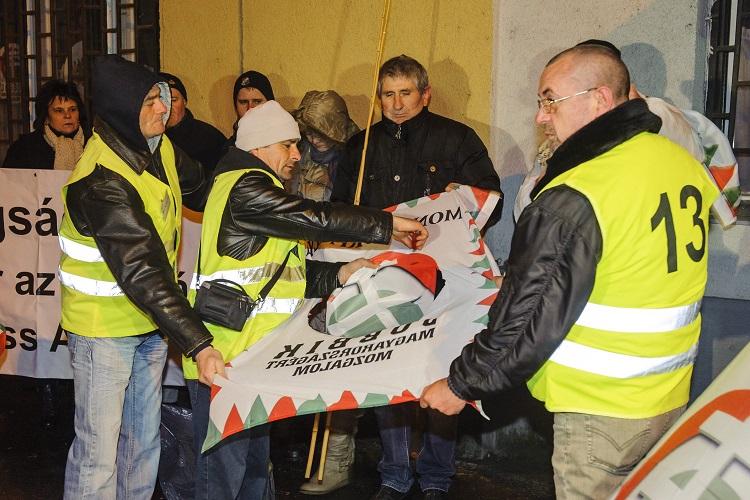 Debrecen, 2017. január 14. A Jobbikból korábban kizárt, vagy kilépett párttagok, egykori alapszervezeti vezetõk a párt zászlajából kivágják az emblémát demonstrációjukon, amelyet a Jobbik jelenlegi politikája és Vona Gábor pártelnök ellen tartottak a párt debreceni irodája elõtt Debrecenben 2017. január 14-én. MTI Fotó: Czeglédi Zsolt