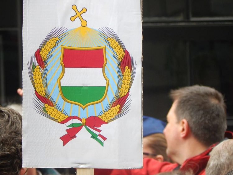 A sign mocking the perceived authoritarian tendencies of the Orbán government, by adding a cross to the top of the seal of the Communist-era People's Republic of Hungary (Photo: 444.hu- Gábor Merkl)